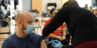 Man receives vaccine shot in arm.