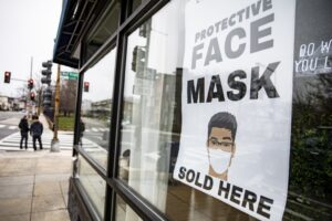 A sign advertising protective face masks is taped in the window of a coronavirus pop-up store.