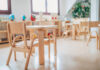 An empty pre-school classroom with wooden desks.