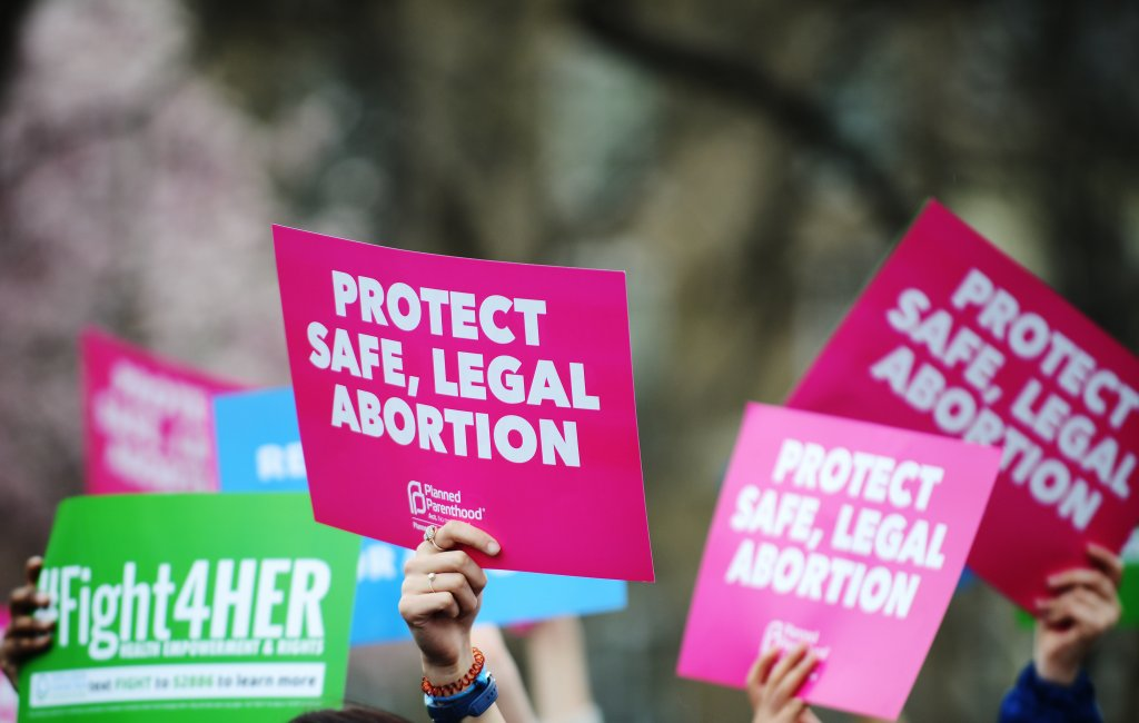 """People hold up signs that read """"Protect safe, legal abortion."""""""
