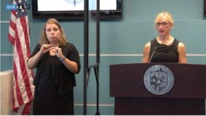 Springfield Greene County Health Department Director Katie Towns stands at a podium addressing reporters while a translator for the hearing impaired signs. The setting is a government meeting room with teal walls and an American flag to the left of the podium.