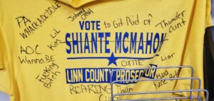 """A yellow T-shirt printed with """"Vote Shiante McMahon Linn County Prosecutor"""" is show defaced with almost a dozen obscene, sexist and racist messages, is shown as it appeared when hung in the Marceline, Missouri, Police Department offices."""