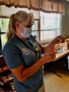 Michele Shull of the Columbia-Boone County Public Health and Humane Services Department is shown in a blue T-shirt using a syringe to draw out a dose of Johnson & Johnson COVID-19 vaccine from a vial.