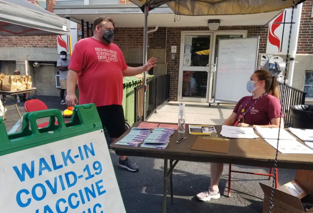 A man in a red shirt is shown standing and speaking to a woman seated at a table outside a COVID-19 vaccination clinic Thursday in Columbia.