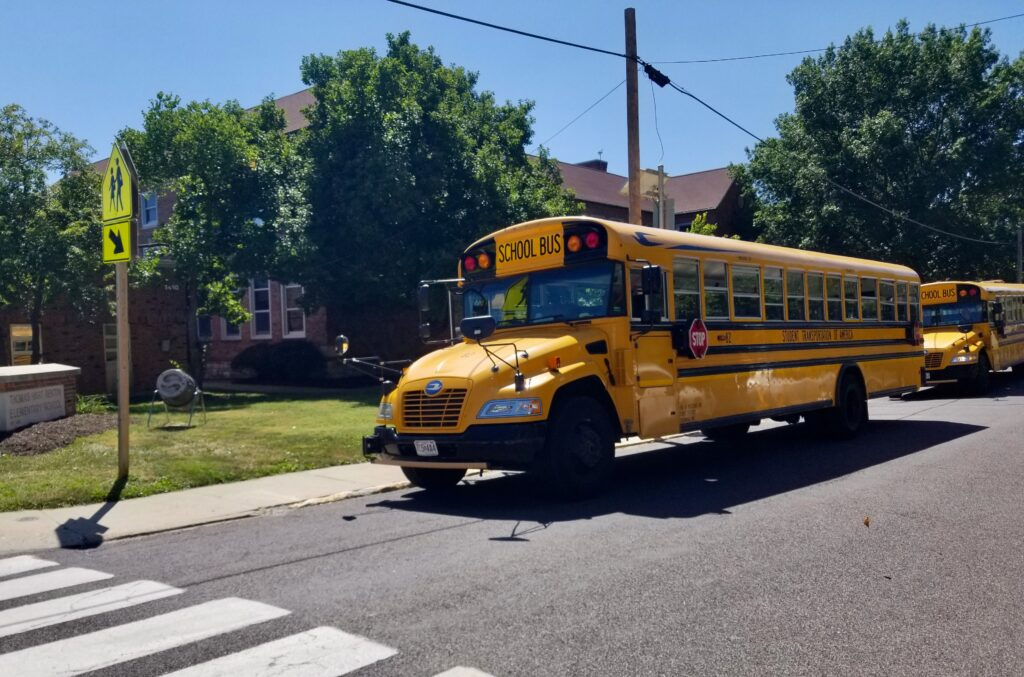 Two yellow school buses are show in bright sunshine outside a two-story brick school building in Columbia, Missouri.