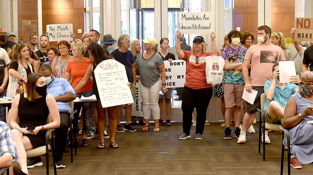 """A large group of people, some wearing masks and some bare-faced, hold signs with slogans like """"no mask, my choice"""" and """"mandates are unconstitutional"""" along the back wall of the Columbia City Council meeting room."""