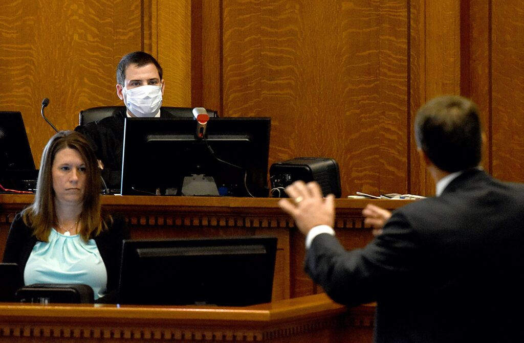 A judge in a face mask is shown looking at an attorney making an argument. The attorney's back is to the camera and the view also shows the female court reporter transcribing the argument.