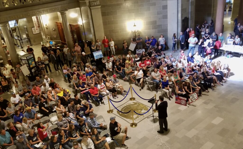 A man with a microphone is addressing a crowd of about 200 to 300 people in the rotunda of the Missouri Capitol.