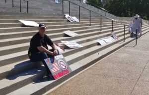 A lone man with a sign that says Stop COVID Mandates sits on the marble steps of the Missouri Capitol Building.