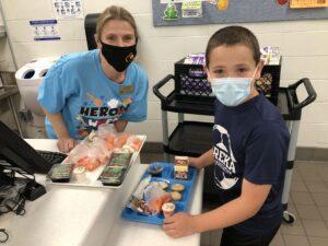 Rockwood Child Nutrition Services staff member Jennifer Fitzpatrick serves lunch to a Eureka Elementary student.