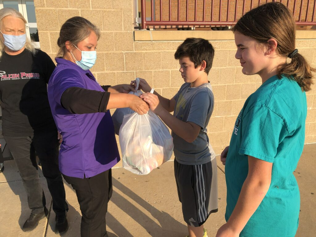 A Rockwood Child Nutrition Services staff member serves a grab-n-go meal bag to two students at Rockwood South Middle.