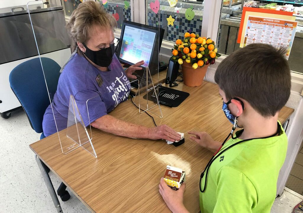 A Rockwood Child Nutrition Services staff member wipes off a finger scanner for a student at Ridge Meadows Elementary.