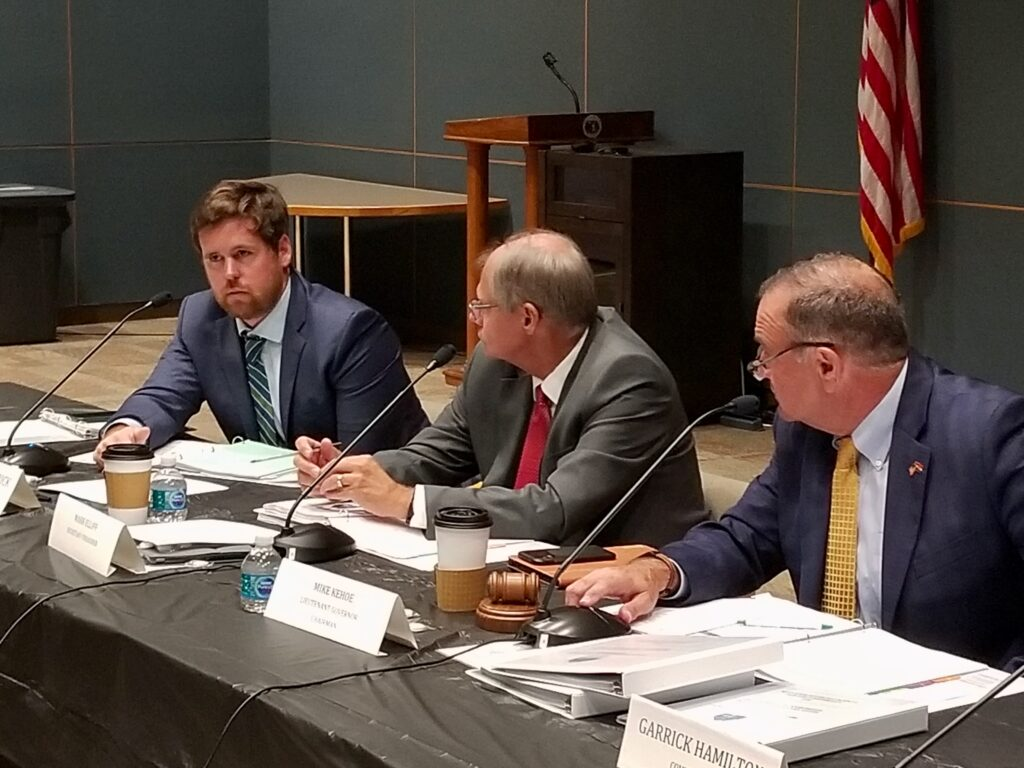 Three members of the Missouri Housing Development Commission, all white men in suits, are showing discussing a policy issue during the Sept. 1, 2021, commission meeting.