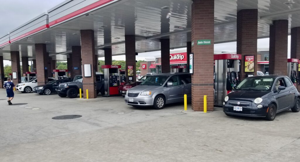 The scene is a busy convenience store with five rows of fuel pumps, almost all busy with cars pumping gas.